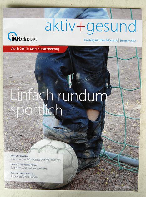 Junge mit löchriger Hose am Tor gelehnt, Fuß auf dem Ball, Titelfoto