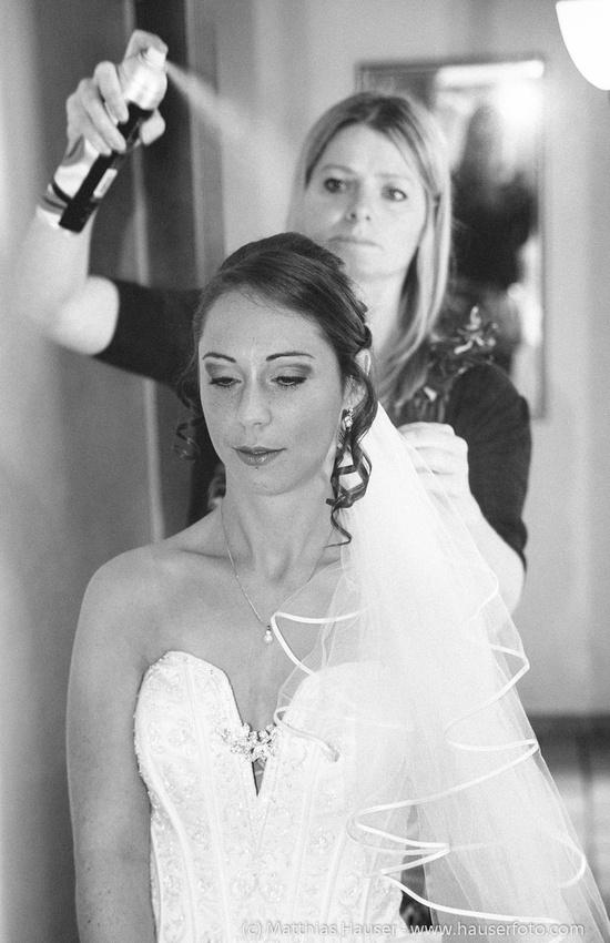 Braut und Visagistin bei den letzten Vorbereitungen, Haarspray wird auf die Haare gesprüht