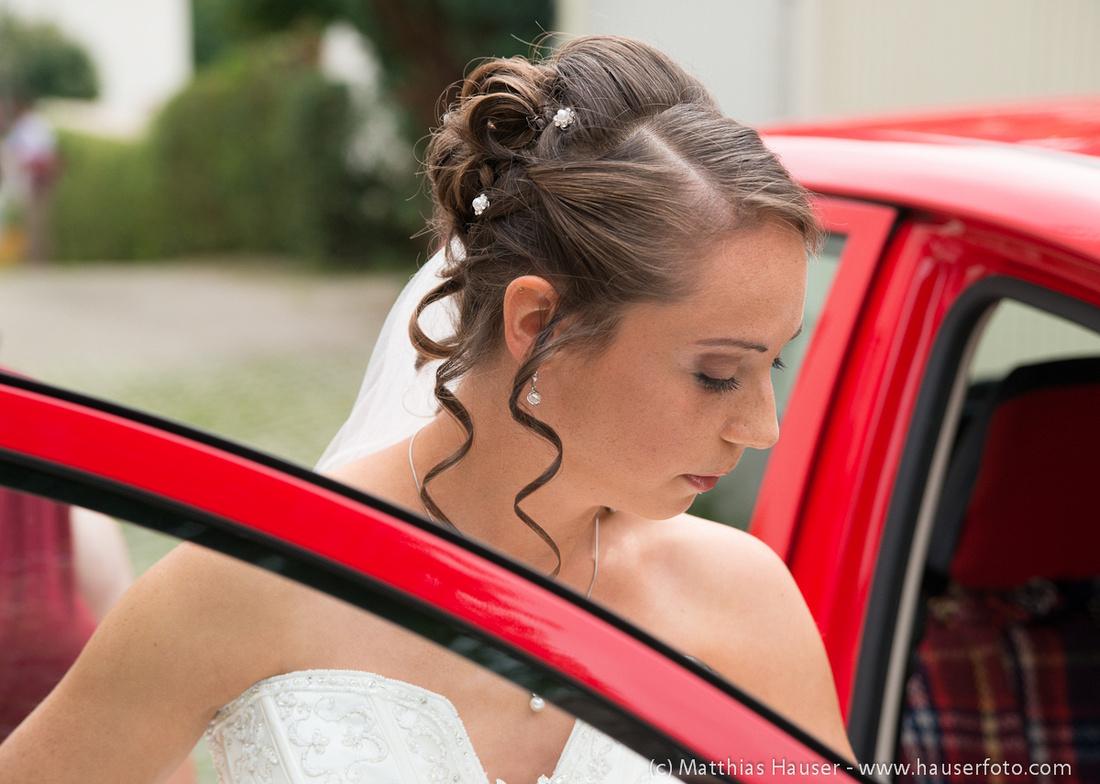 Hochzeit - Porträt der Braut beim Einsteigen ins Auto