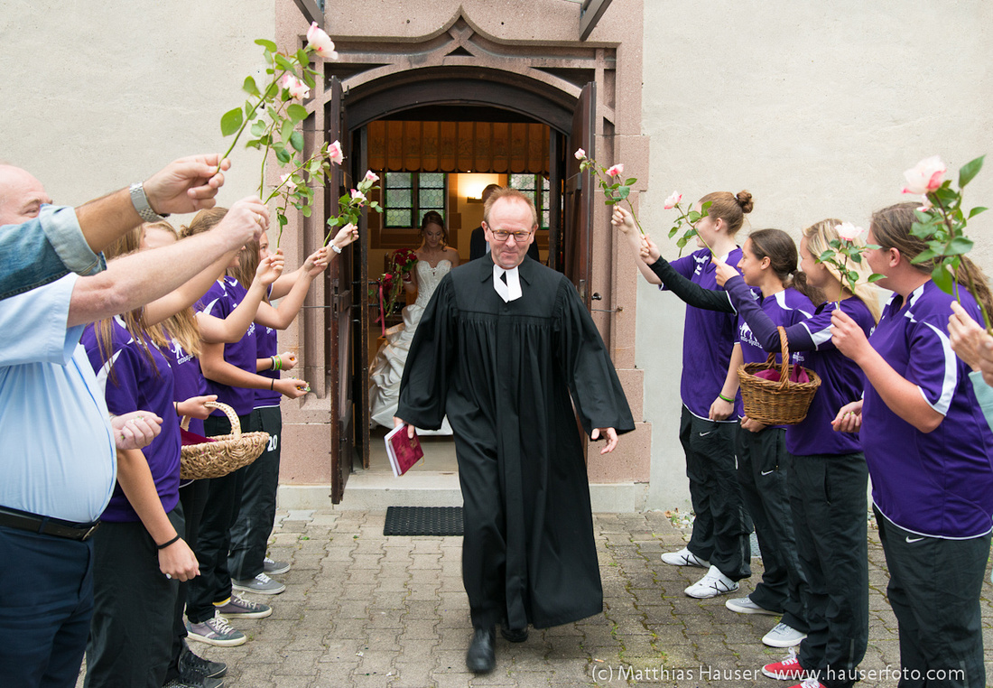 Hochzeit - Pfarrer durchschreitet ein Spalier vor der Kirche