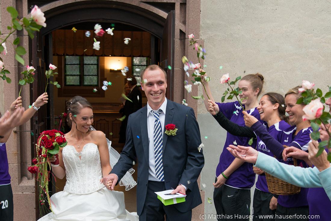 Das Hochzeitspaar beim Auszug aus der Kirche, Freunde und Bekannte stehen Spalier, fröhliche Stimmung