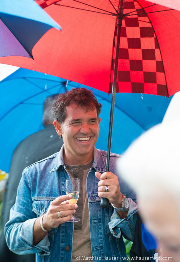 Lachender Mann mit Regenschirm bei Hochzeit