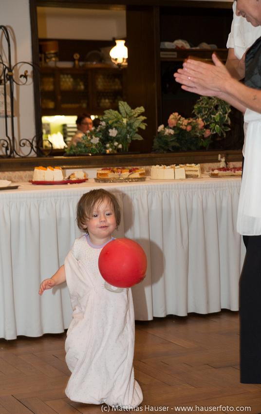 Kind mit Luftballon tanzt auf einer Hochzeitsfeier