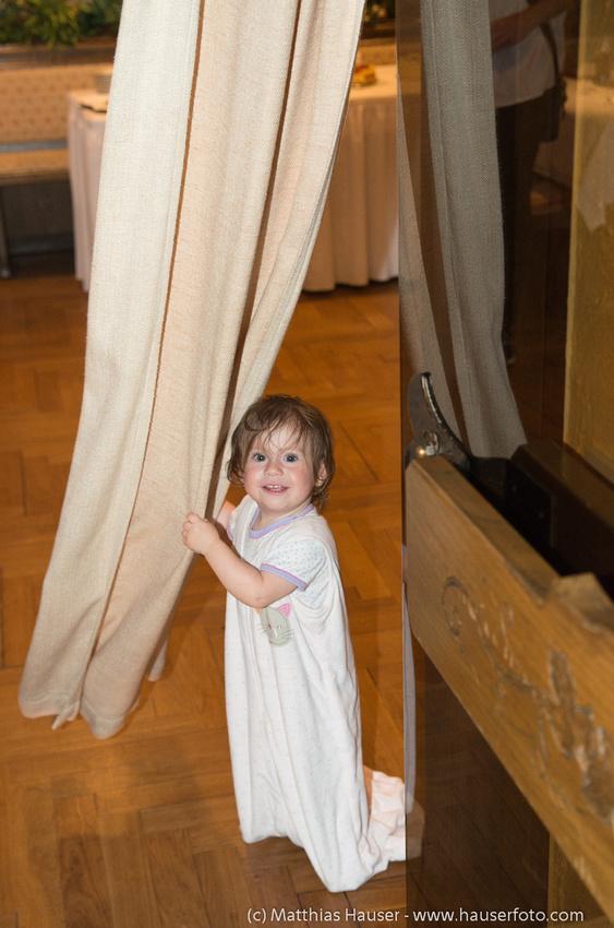Kind spielt mit Vorhang