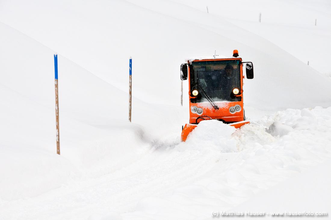 Schnee räumen - Räumfahrzeug bahnt eine Straße im Winter