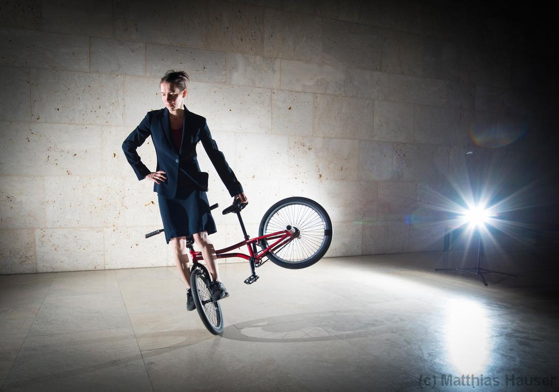 Cool and elegant: BMX Flatland Artist Monika Hinz rides on her bike with a classy dress, a flashlight illuminates the scenery