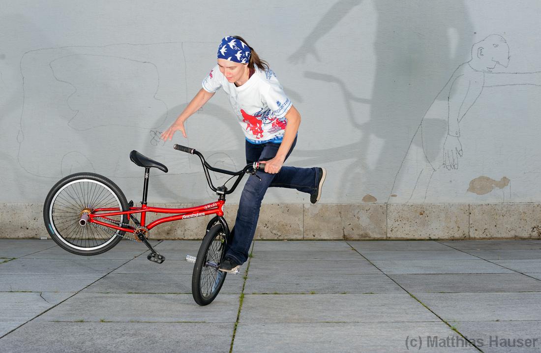 Red bike, stylish cloth and a shadow: Monika Hinz riding BMX Flatland
