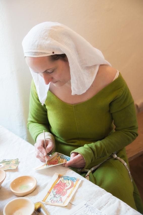 Altes historisches Handwerk: Frau mit Kopftuch und grünem Kleid malt ein Bild