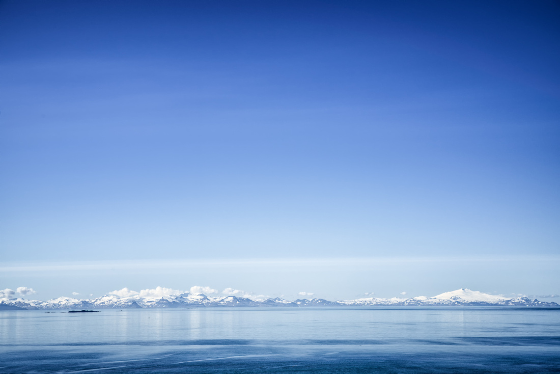 Blue sky and water and snow-covered mountains in Iceland