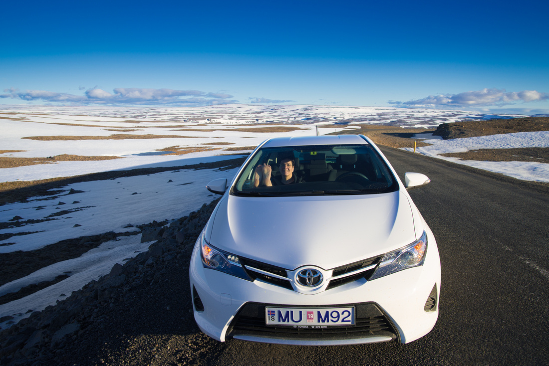 Car on a road in Iceland - snow in June