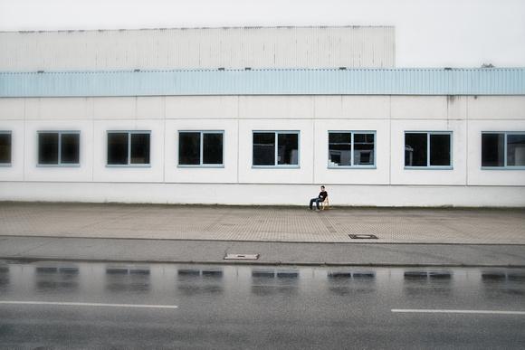 Einsame Person sitzt auf einem Stuhl vor einem Gebäude an einer Straße