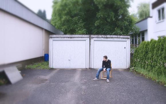 Junge sitzt auf einem Stuhl vor einer Garage