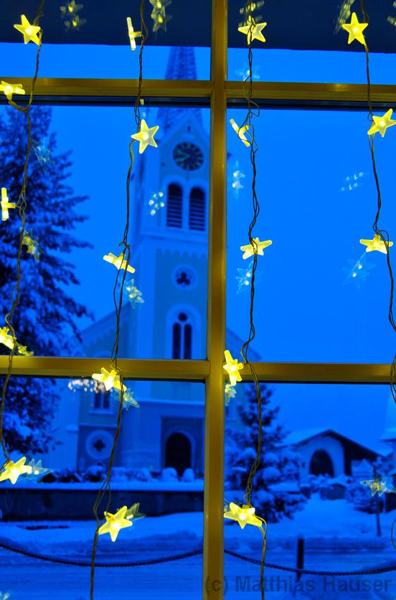 Weihnachtsdekoration, geschmücktes Fenster mit gelben Sternen, dahinter die Kirche in Riezlern, Kleinwalsertal am frühen Morgen zur blauen Stunde