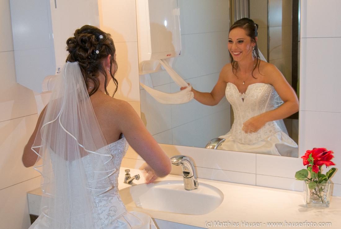 Lachende Braut im Hochzeitskleid vor dem Spiegel