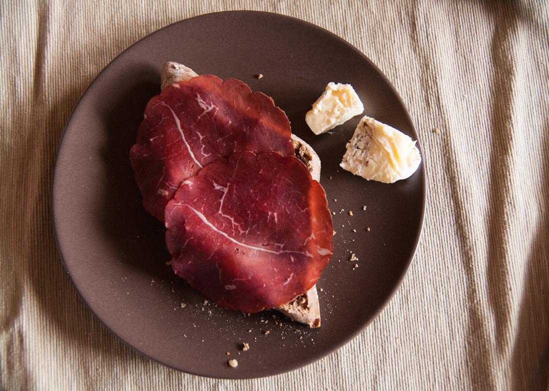 Deftiges Frühstück oder Vesper - Schweizer Bündnerfleisch und Käse auf einem Teller
