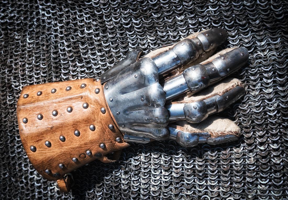 Alter Handschuh eines Ritters liegt auf einem silbernen Kettenhemd