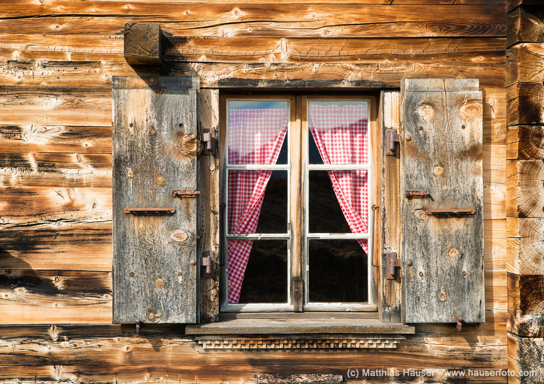 Rustic cabin detail - wooden facade and window with red curtain