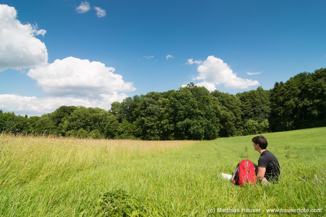 Frau mit rotem Rucksack sitzt auf einer grünen Wiese - Naturpark Schönbuch