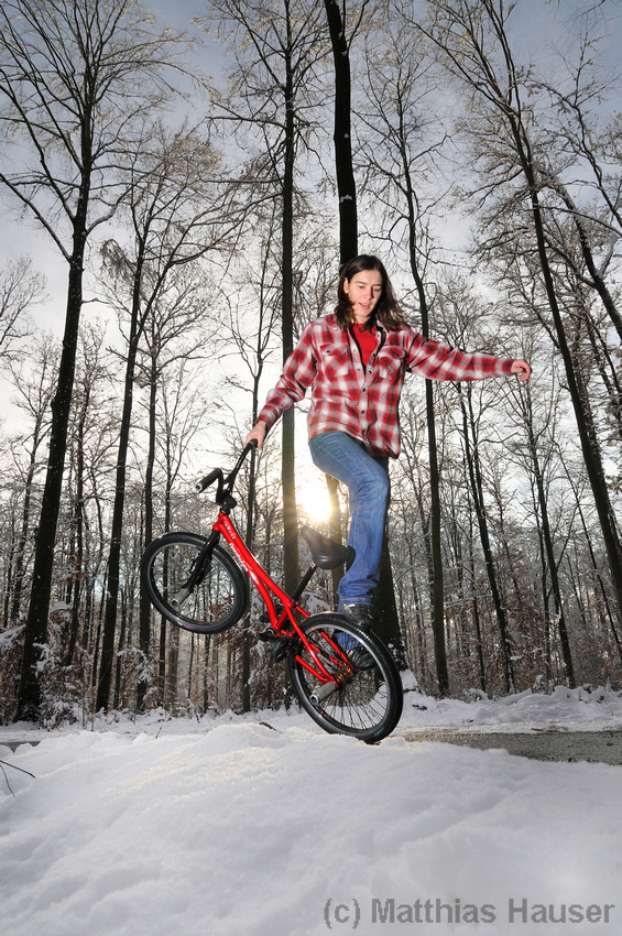 Monika Hinz with her red bike in the winterly forest, riding BMX Flatland in winter with lots of snow