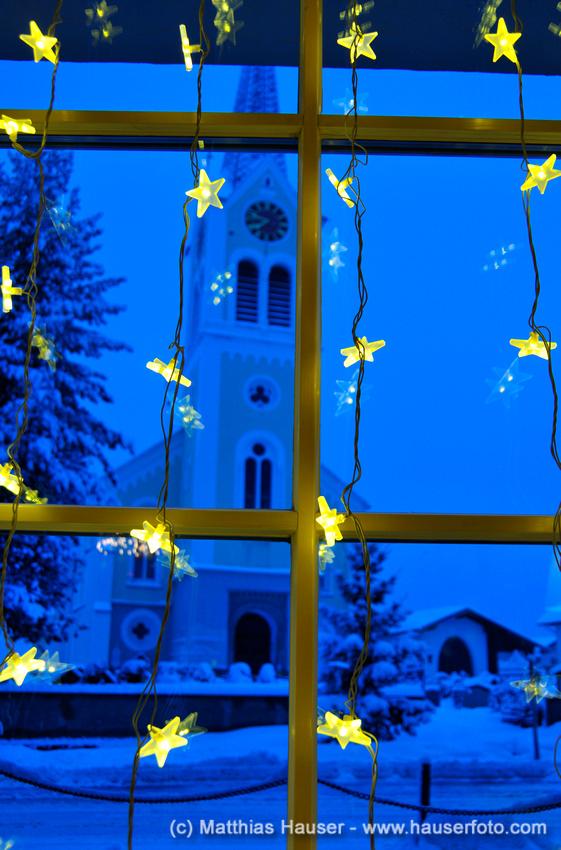 Weihnachtlich geschmücktes Fenster, Ausblick auf die Kirche in Riezlern, Kleinwalsertal, Österreich