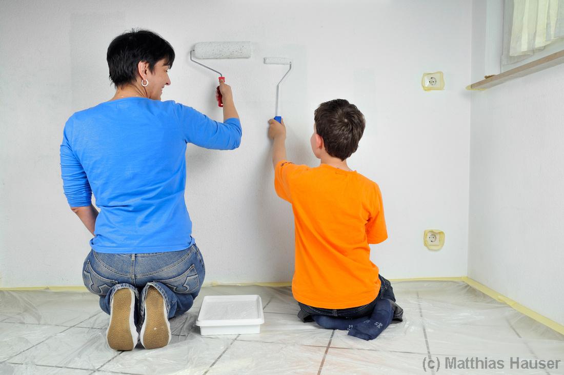 Frau und Kind streichen gemeinsam eine Wand - Renovierung, Teamwork, Malerarbeiten